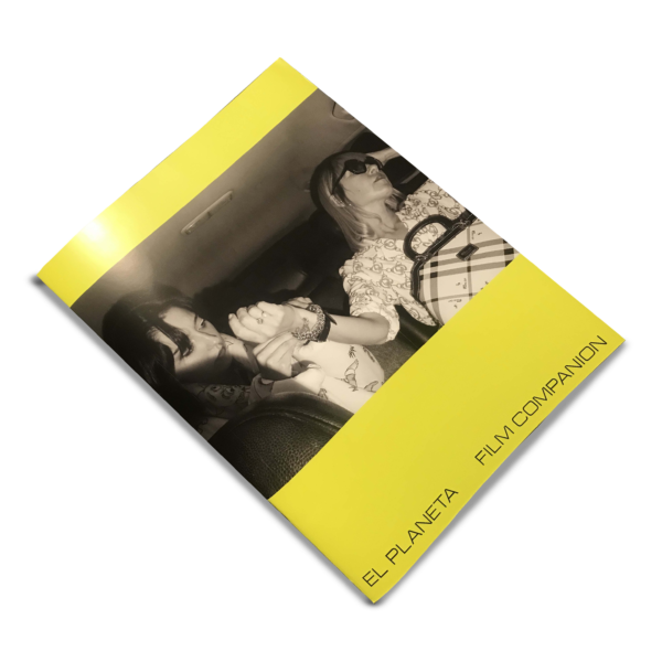 a yellow saddle-stitched book hovers diagonally across the the frame, a photo of two women in the interior of a car takes up most of the cover, a line of text along the bottom reads 'EL PLANETA FILM COMPANION